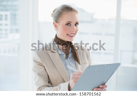 Blonde smiling businesswoman holding clipboard in bright office - stock photo