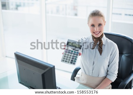 Blonde smiling businesswoman showing calculator in bright office