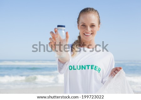 Blonde smiling volunteer picking up trash on the beach on a sunny day - stock photo