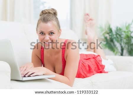 Blonde smiling while relaxing on the sofa and using the notebook