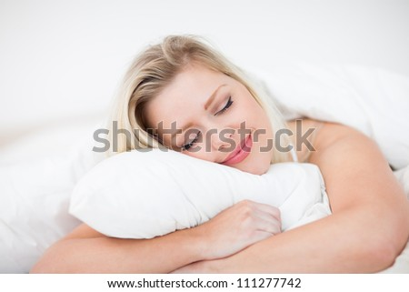 Blonde smiling while sleeping in a bed - stock photo