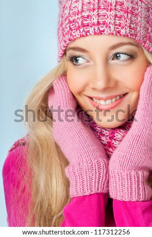 blonde smiling woman wearing pink knitwear over blue background - stock photo