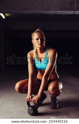 Blonde sportswoman crouching with a kettlebell in her hands - stock photo
