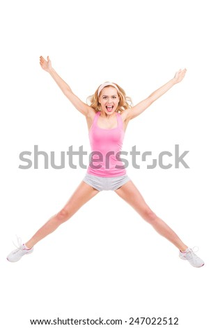 Blonde star. Full length of beautiful blond hair woman in pink sports clothing keeping arms and legs outstretched while jumping against white background - stock photo