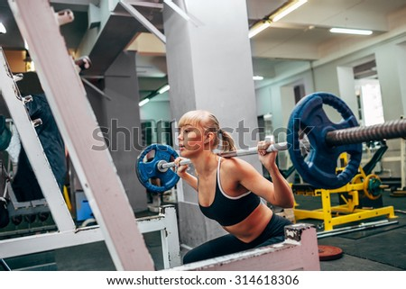 blonde strong fitness woman doing barbell squats in a gym - stock photo