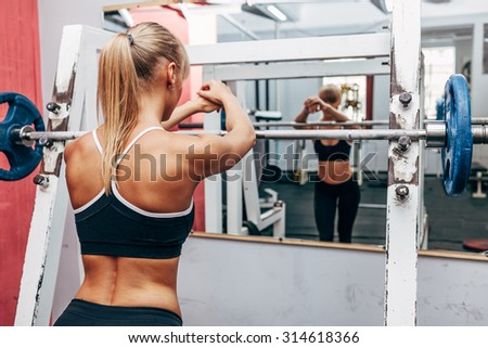 blonde strong fitness woman preparing for barbell squats in a gym - stock photo
