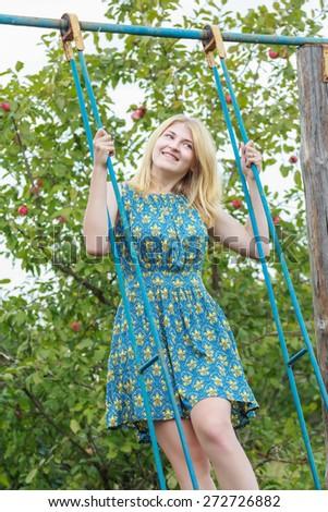 Blonde student girl in azure blue silk sundress is standing on handmade swing - stock photo