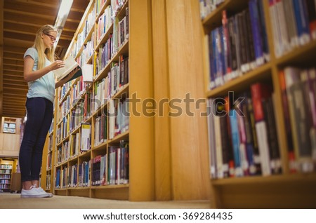 Blonde Student Reading Book Next To Bookshelf In Library