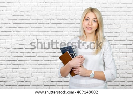 Blonde student with stack of books - stock photo