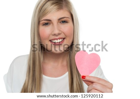 Blonde teen presenting creative pink paper heart to the camera. Love concept