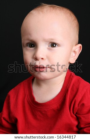 Blonde toddler against a black background with a serious expression - stock photo