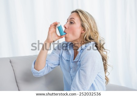 Blonde using her asthma inhaler on couch at home in the living room - stock photo
