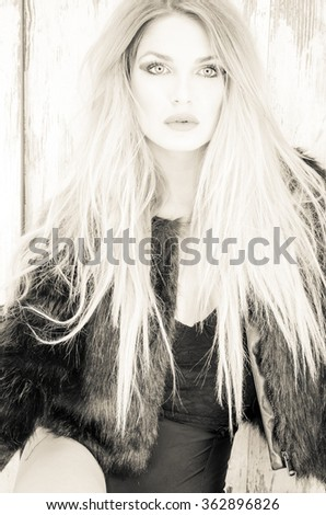 Blonde with a black coat and long blond hair posing in the studio