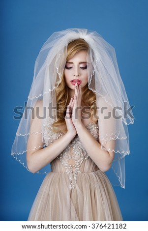 Blonde with a red heart in an elegant evening dress. Valentines Day. Love. Fashion beautiful woman with red heart balloon on a blue background. Beautiful bride in wedding day. Wedding dress.  - stock photo