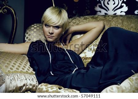 blonde with short hair lying on the sofa of expensive fabric. she is beautiful, dreamy and sexy. She is wearing a sleeveless evening dress made of silk.  - stock photo