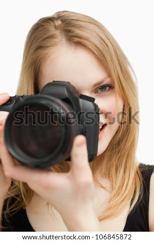 Blonde woman aiming with a camera against white background - stock photo
