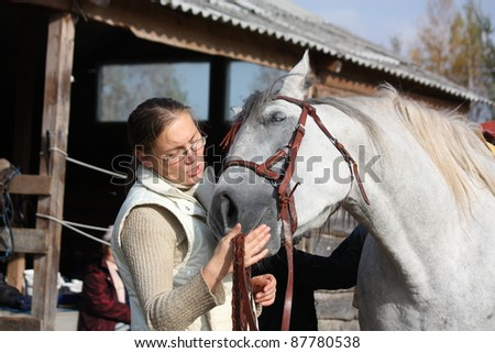Blonde woman and white horse - stock photo