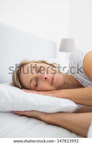 Blonde woman asleep in bed at home in bedroom