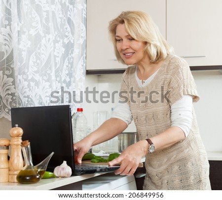 Blonde woman  cooking  with notebook in home kitchen