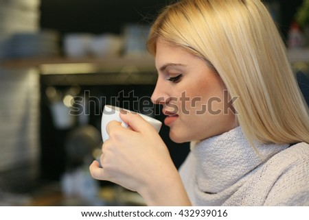 Blonde woman drinking coffee in the kitchen. - stock photo