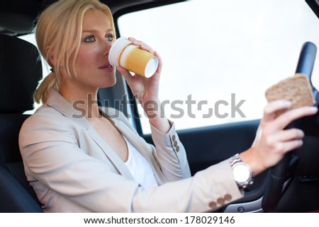 Blonde woman drinking coffee while driving. - stock photo