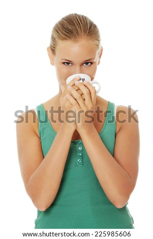 Blonde woman drinking from cup - stock photo