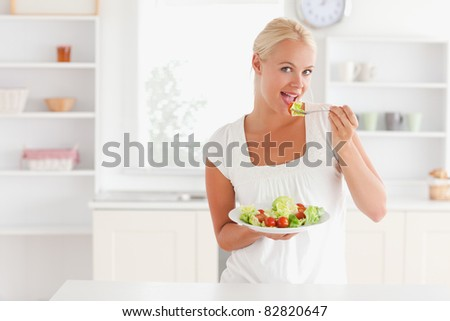 Blonde woman eating a salad in her kitchen
