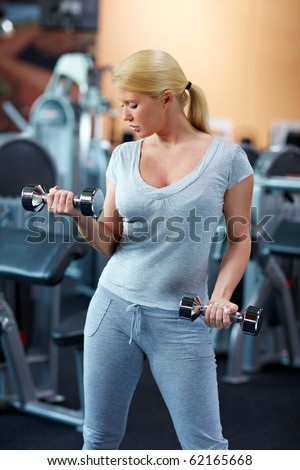 Blonde woman exercising in gym with dumbbells - stock photo