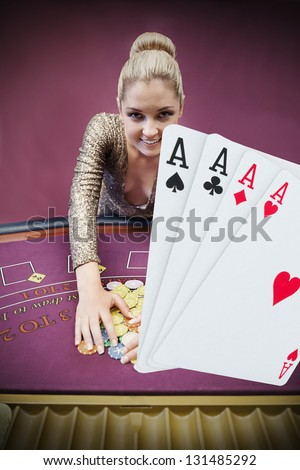 Blonde woman grabbing chips with digital hand of four aces at the foreground in the casino - stock photo