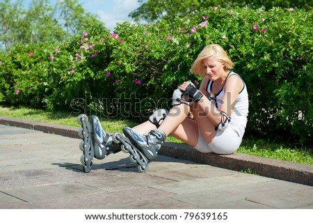 Blonde woman has hit a knee skating on roller-skaters and it hurts - stock photo