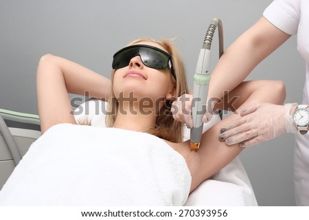 Blonde woman having underarm Laser hair removal epilation. Laser treatment in cosmetic salon - stock photo