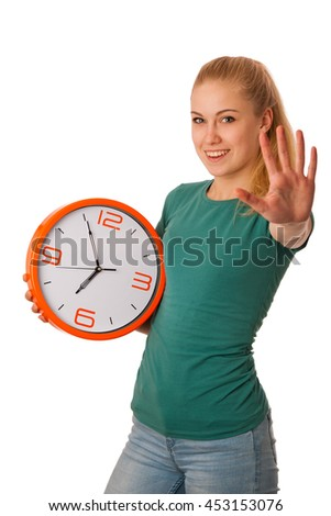 Blonde woman holding big clock in hand, gesturing five minute to seven o'clock, isolated over white.