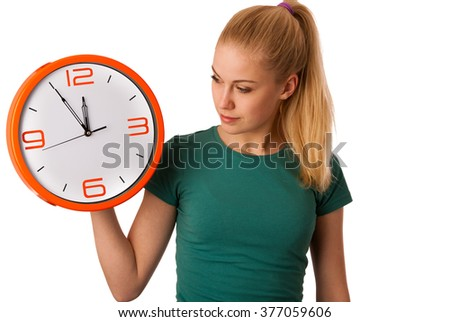 Blonde woman holding big clock in hand, watching how much is the time isolated over white.