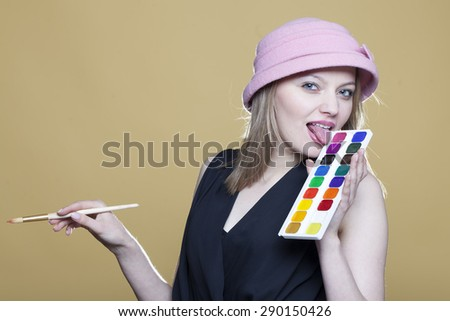 Blonde woman holds paint and brush on beige background - stock photo