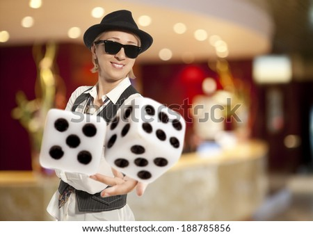 Blonde Woman in a hat playing dice  - stock photo