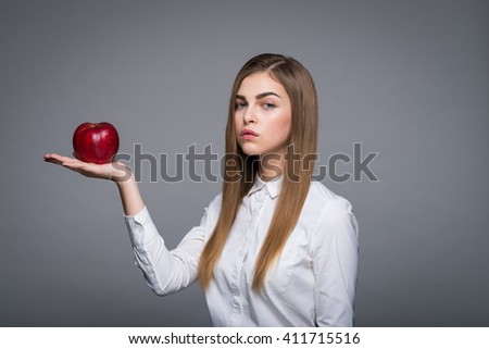 blonde woman in a white blouse holding hand red apple, fashion portrait