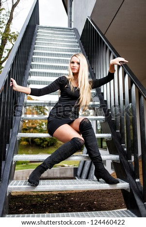 Blonde woman in black short dress sitting on staircase. - stock photo