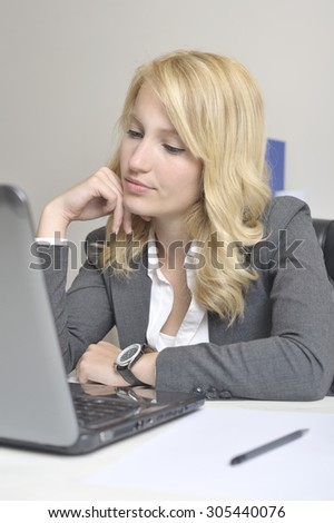 Blonde woman in doubt behind a laptop at work.