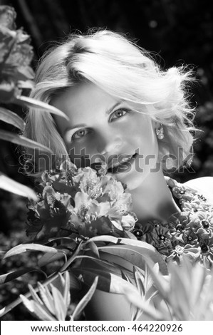 blonde woman in park with blooming rhododendrons flowers