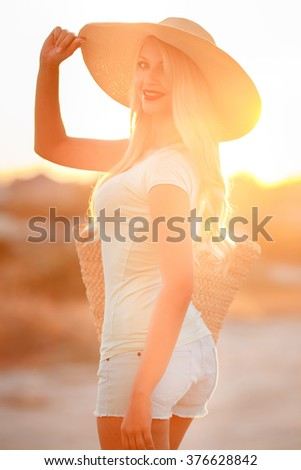blonde woman in straw hat in sunset light. Young and beautiful woman wearing a hat in sunset light looking far away. Photo from behind. the girl is happy summer sun - stock photo