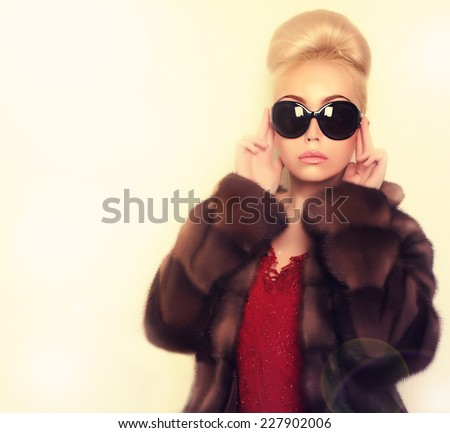 blonde woman in sunglasses wearing mink fur coat .