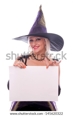Blonde woman in the witch costume holding blank paper in her hand and showing with index finger on the blank space - stock photo
