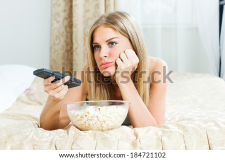 Blonde woman is feeling lazy,she is trying to find something interesting on tv to pay her attention,but there is nothing interesting,I'm so bored! - stock photo