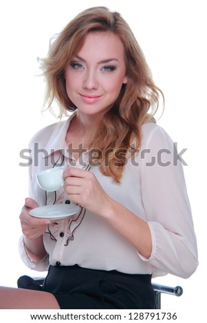 Blonde woman is holding coffee cup and sitting on a stool - stock photo