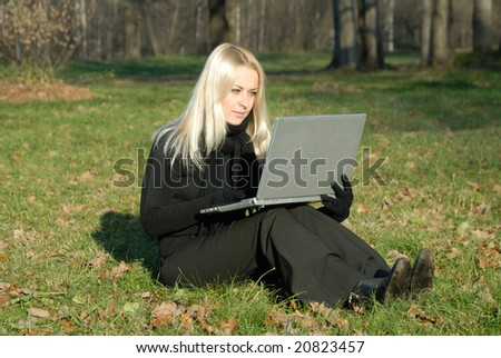 blonde woman is sitting on green grass with notebook in the park, autumn,