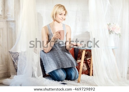 Blonde woman kneeling at home on floor, using laptop computer, drinking tea.