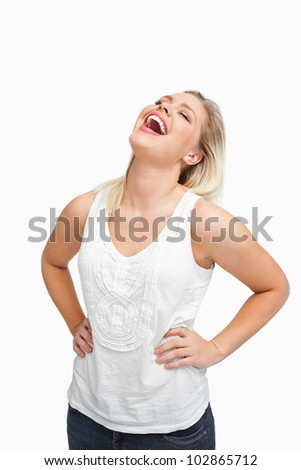 Blonde woman laughing while placing her hands on her hips against a white background - stock photo