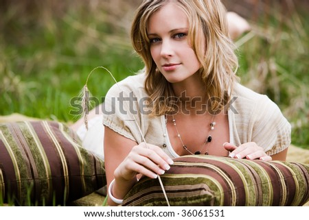 Blonde woman laying on the grass holding a weed - stock photo