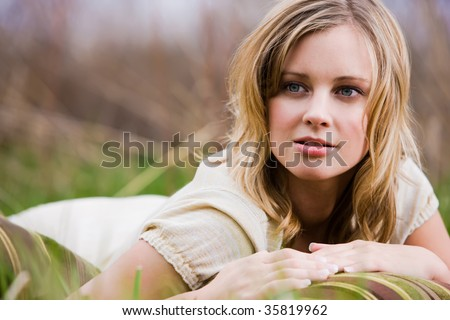 Blonde Woman laying on the grass on her stomach with a pillow - stock photo