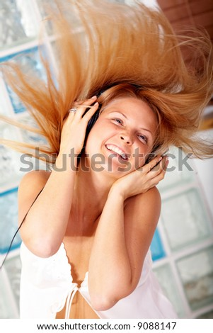blonde woman listening to music looking happy at home - stock photo